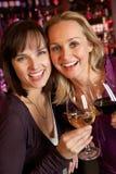 Dos mujeres que disfrutan de la bebida junto en barra fotografía de archivo libre de regalías