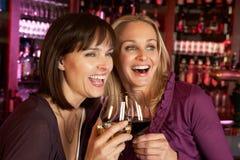 Dos mujeres que disfrutan de la bebida junto en barra Foto de archivo libre de regalías