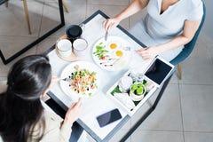 Dos mujeres que disfrutan de la comida en café imagen de archivo libre de regalías