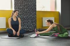 Dos mujeres que ejercitan en el club de fitness imagen de archivo