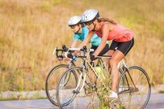 Dos mujeres que ejercitan en las bicicletas al aire libre. imagen horizontal Foto de archivo