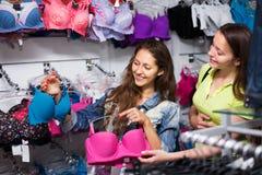 Dos mujeres que eligen la ropa interior en tienda Imagen de archivo libre de regalías