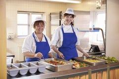 Dos mujeres que esperan para servir el almuerzo en una cafetería de la escuela imagenes de archivo