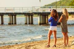 Dos mujeres que hablan la reclinación sobre la playa Fotografía de archivo
