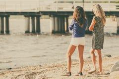 Dos mujeres que hablan la reclinación sobre la playa Fotos de archivo libres de regalías