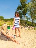 Dos mujeres que hablan la reclinación sobre la playa Imágenes de archivo libres de regalías