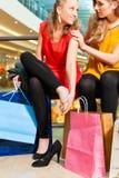 Dos mujeres que hacen compras con los bolsos en alameda Imagen de archivo