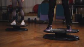 Dos mujeres que hacen ejercicio en el cuarto aerobio con el uso del tablero de base almacen de metraje de vídeo