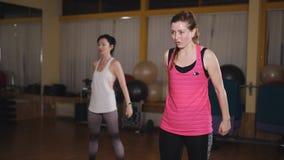 Dos mujeres que hacen ejercicio en el cuarto aerobio con el uso del tablero de la balanza almacen de metraje de vídeo