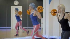 Dos mujeres que hacen estocadas con el barbell en gimnasio almacen de metraje de vídeo