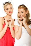 Dos mujeres que hacen forma del corazón aman símbolo con las manos Foto de archivo libre de regalías