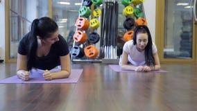 Dos mujeres que hacen la correa del ejercicio en sus codos en la clase del deporte almacen de metraje de vídeo
