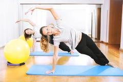 Dos mujeres que hacen una aptitud exercisen en synchrony Fotografía de archivo