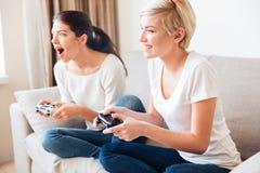 Dos mujeres que juegan a los videojuegos imagen de archivo libre de regalías