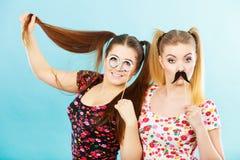 Dos mujeres que llevan a cabo accessoies del carnaval en el palillo Imagen de archivo libre de regalías