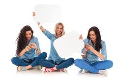 Dos mujeres que mandan un SMS en los teléfonos y uno llevan a cabo burbujas del discurso Foto de archivo