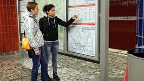 Dos mujeres que miran el mapa del metro del subterráneo Foto de archivo libre de regalías