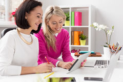 Dos mujeres que miran la tableta mientras que trabaja en oficina Imagen de archivo libre de regalías