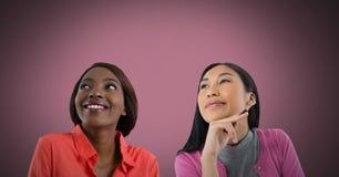Dos mujeres que miran para arriba con el fondo rosado Fotos de archivo
