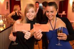 Dos mujeres que presentan boletos del teatro o de la película Imagenes de archivo