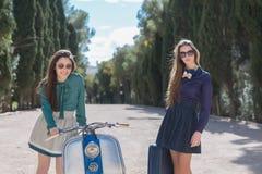 Dos mujeres que presentan cerca de la moto retra Foto de archivo libre de regalías