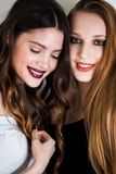 Dos mujeres que ríen en un fondo blanco Emociones positivas, características faciales expresivas, alegría, felicidad, concepto de Fotos de archivo libres de regalías