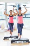 Dos mujeres que realizan ejercicio de los aeróbicos del paso con pesas de gimnasia Imagen de archivo libre de regalías