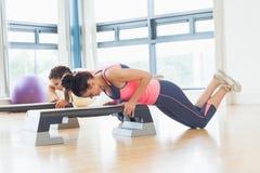 Dos mujeres que realizan ejercicio de los aeróbicos del paso en gimnasio Fotos de archivo libres de regalías