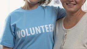 Dos mujeres que señalan en la palabra voluntaria en la camiseta, trabajos de la oferta de ayudar a gente almacen de video