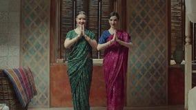 Dos mujeres que se acercan el uno al otro para saludar metrajes
