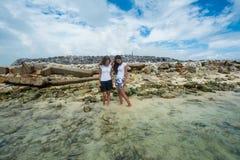 Dos mujeres que se colocan en el océano cerca de descarga de basura y que llevan a cabo las manos fotografía de archivo