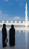 Dos mujeres que se colocan en la mezquita magnífica Sheikh Al Zayed en Abu Dhabi Foto de archivo