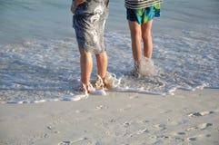 Dos mujeres que se colocan en la playa Fotos de archivo libres de regalías