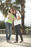 Dos mujeres que se divierten bajo las palmeras Imagen de archivo libre de regalías