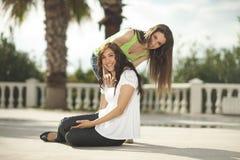 Dos mujeres que se divierten bajo las palmeras Foto de archivo