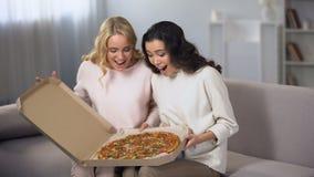 Dos mujeres que se divierten en casa, abriendo la caja de la pizza, entrega de la comida, partido casero almacen de video