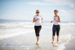 Dos mujeres que se ejecutan en la playa Fotos de archivo