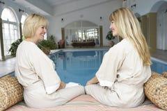 Dos mujeres que se relajan por la piscina Imágenes de archivo libres de regalías