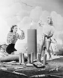 Dos mujeres que se sientan alrededor del fuego trabajan (todas las personas representadas no son vivas más largo y ningún estado  fotos de archivo