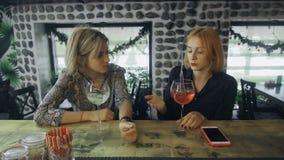 Dos mujeres que se sientan cerca de contador de la barra con los cócteles del alcohol que tienen conversación interesante almacen de metraje de vídeo