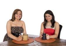 Dos mujeres que se sientan comiendo café en la tabla Imagen de archivo libre de regalías