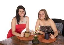 Dos mujeres que se sientan comiendo café en la tabla Foto de archivo libre de regalías