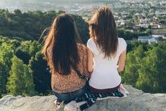 Dos mujeres que se sientan en el pico y el lookin en ciudad ajardinan Imagen de archivo libre de regalías