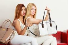 Dos mujeres que se sientan en el sofá que presenta bolsos Fotos de archivo