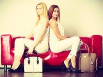 Dos mujeres que se sientan en el sofá que presenta bolsos Fotografía de archivo