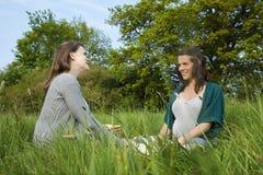 Dos mujeres que se sientan en hierba Imágenes de archivo libres de regalías