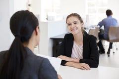 Dos mujeres que se sientan en una entrevista en una oficina abierta del plan fotos de archivo libres de regalías