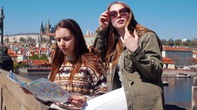 Dos mujeres que sientan en el puente un fondo del centro de la ciudad de Praga y que miran el mapa almacen de video