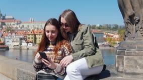 Dos mujeres que sientan en el puente un fondo del centro de la ciudad de Praga y que miran la pantalla del teléfono almacen de video