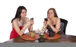 Dos mujeres que sientan los teléfonos celulares del café Imágenes de archivo libres de regalías